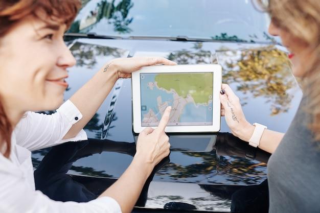 Amis discutant de la carte sur tablette