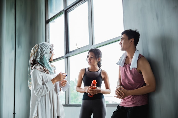 Amis discutant dans la salle de gym après avoir fait de l'exercice ensemble