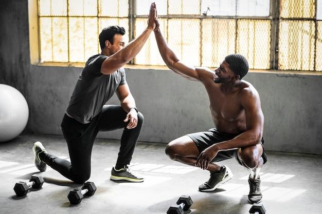 Amis donnant des high five dans une salle de sport