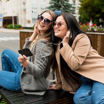 Amis écoutant de la musique avec des écouteurs à l'extérieur
