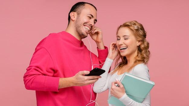 Amis avec des écouteurs en riant