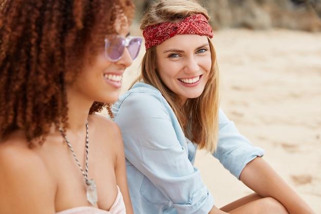 Amis élégants assis sur la plage