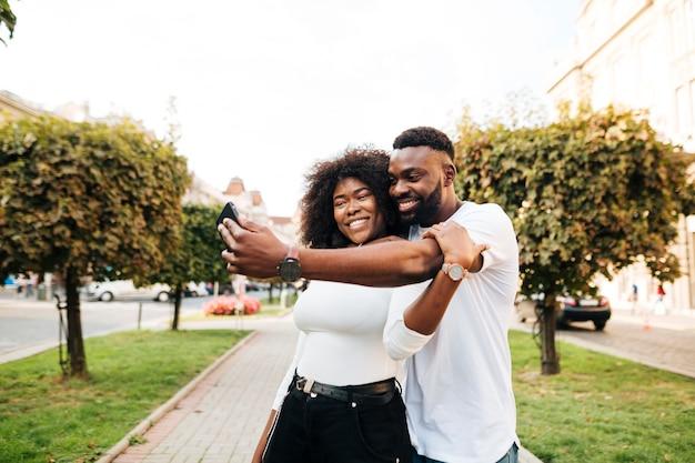 Amis embrassant et prenant selfie