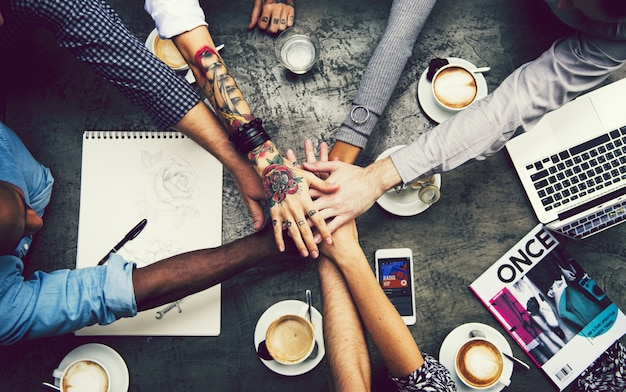 Amis empiler des mains dans un café