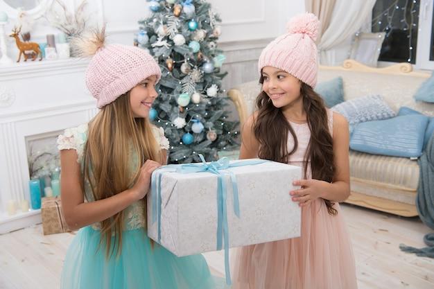 Amis enfants excités en déballant leurs cadeaux. les petites sœurs des enfants tiennent un fond intérieur de boîtes-cadeaux. quelle belle surprise. les petites filles mignonnes ont reçu des cadeaux de vacances. meilleurs jouets et cadeaux de noël.