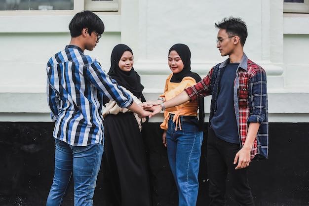 Amis étudiants faisant une pile de mains pour la poignée de main de l'équipe