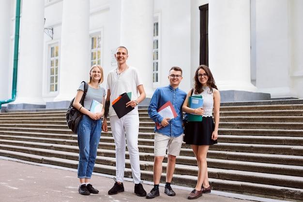Des amis étudiants masculins et féminins souriants se tiennent en plein air près de l'entrée de l'université