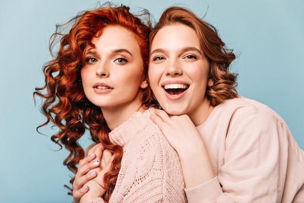 Amis extatiques embrassant sur fond bleu. photo de studio de filles joyeuses regardant la caméra.