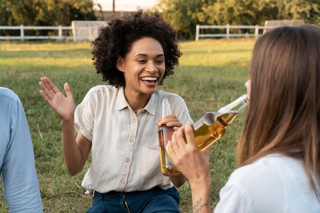 Amis à l'extérieur dans le parc prenant une bière ensemble