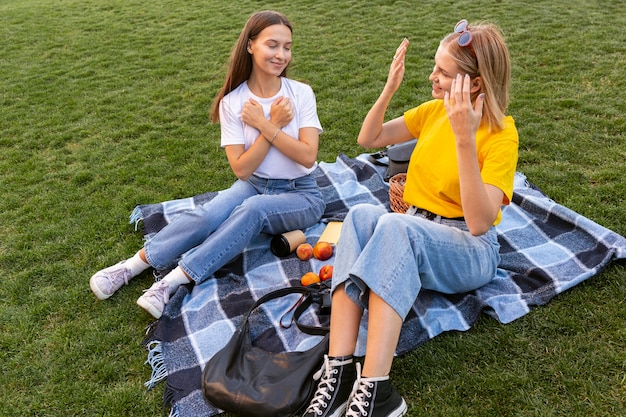 Amis à l'extérieur en utilisant la langue des signes pour communiquer entre eux