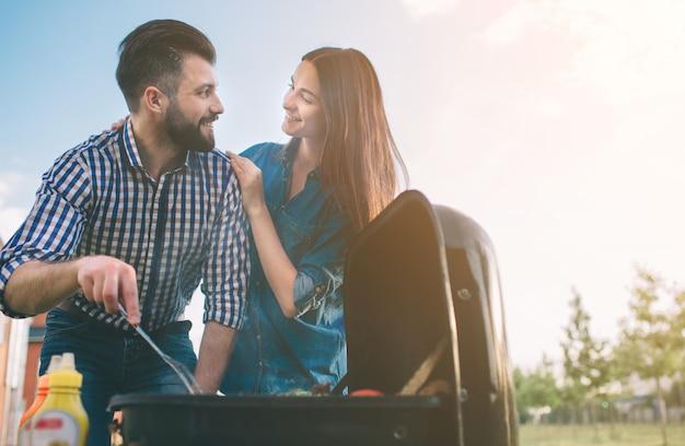 Amis faire un barbecue et déjeuner dans la nature. couple s'amusant tout en mangeant et en buvant à un pique-nique - des gens heureux au barbecue.