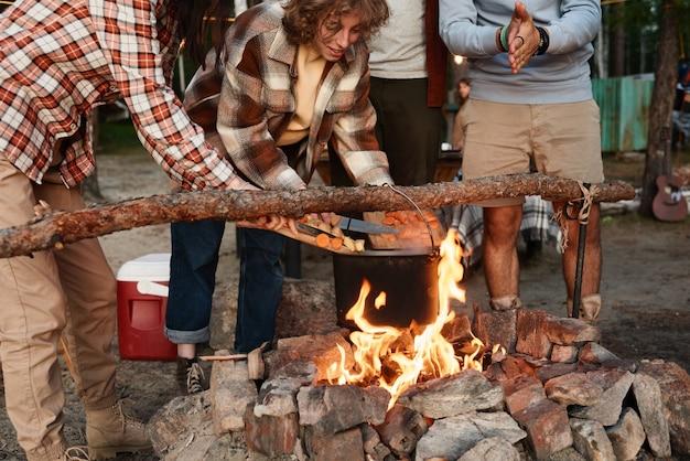 Amis faisant cuire la nourriture ensemble sur un feu pendant le pique-nique dans la forêt