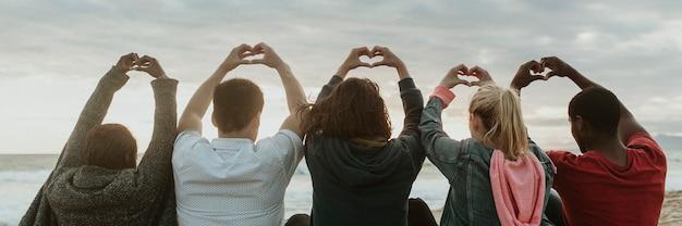 Amis faisant des mains de coeur d'amour à la plage