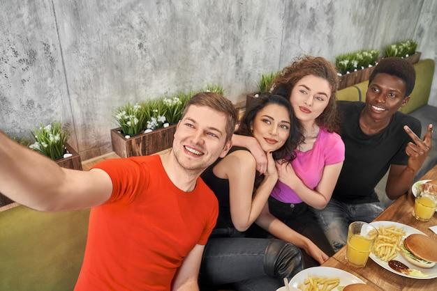 Amis faisant selfie, assis ensemble dans un café.