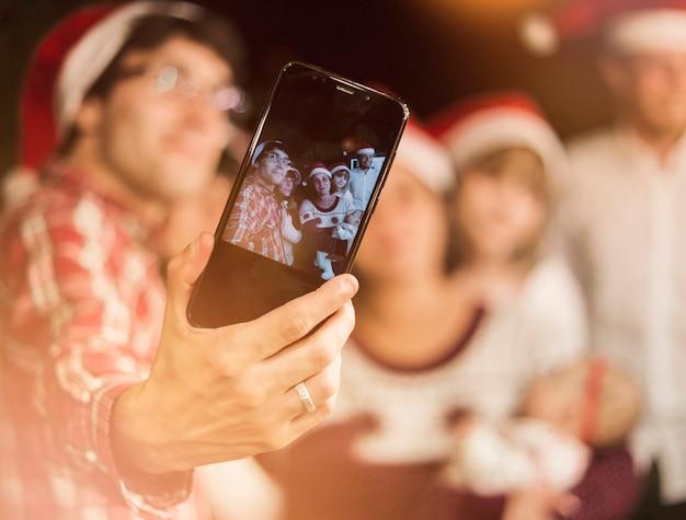 Amis faisant selfie dans des chapeaux de père noël