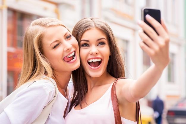 Amis faisant selfie. deux belles jeunes femmes faisant selfie et grimaçant