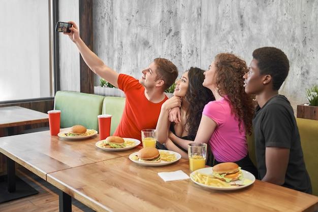 Amis faisant selfie sur téléphone au café.
