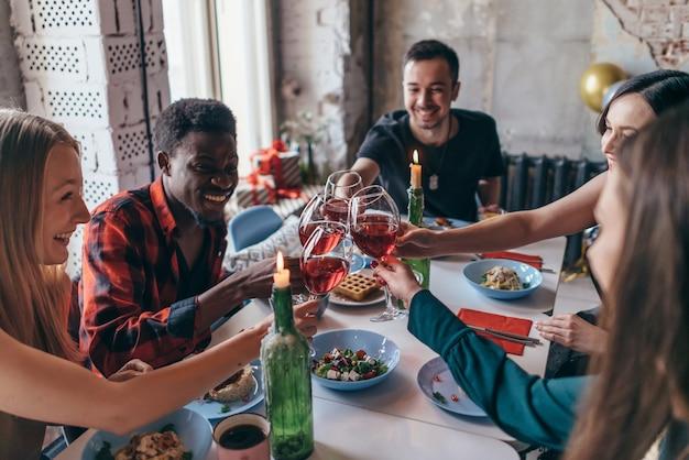 Amis faisant des toasts trinquant au-dessus de la table du dîner.