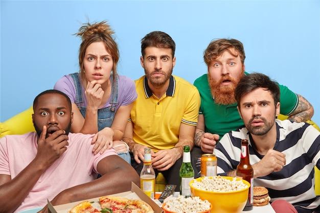 Des amis fascinés regardent l'écran, regardent un film d'horreur ensemble à la maison, passent une soirée de week-end dans une atmosphère domestique