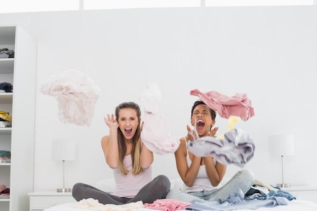 Amis féminines surpris avec des vêtements sur le lit