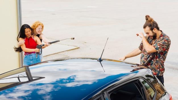 Amis femmes éclaboussures d'eau sur un homme derrière la voiture