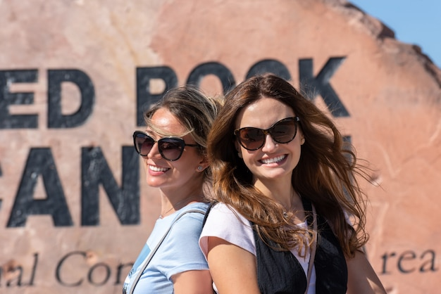 Amis de femmes smiling portrait at red rock desert stone