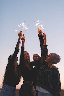Amis avec des feux de bengale en soirée
