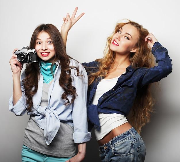 Amis de filles heureux prenant des photos, avec appareil photo, sur gris