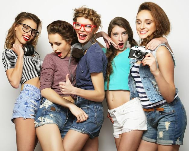 Amis de filles heureux prenant des photos, sur gris