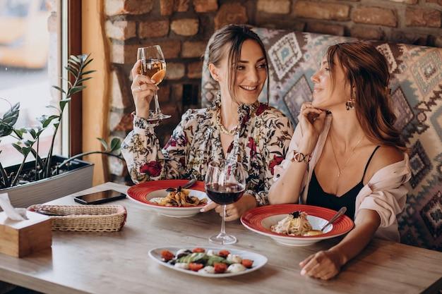 Amis de filles manger des pâtes dans un restaurant italien