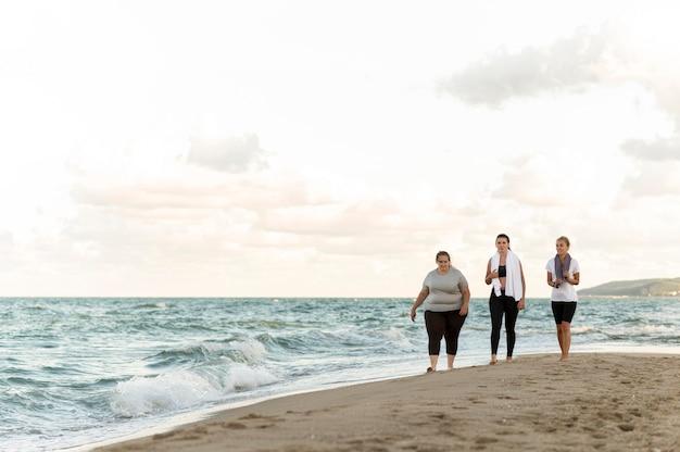 Amis de fitness long shot marchant sur le rivage