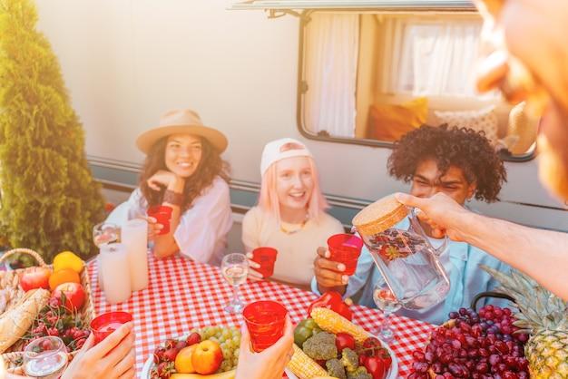 Des amis font un pique-nique avec un camping-car par une journée ensoleillée