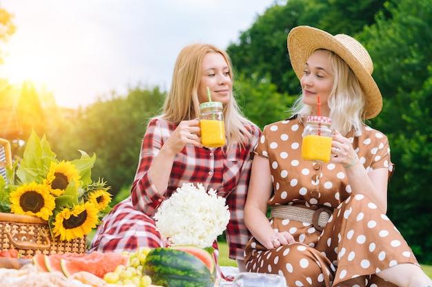 Des amis font un pique-nique en plein air des filles qui rient assises sur une couverture de pique-nique en tricot blanc buvant du vin h ...