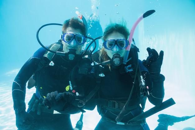 Amis sur la formation de plongée submergé dans la piscine à la recherche de caméra