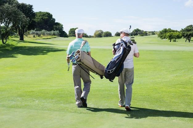 Amis golfeurs marchant avec leurs sacs de golf