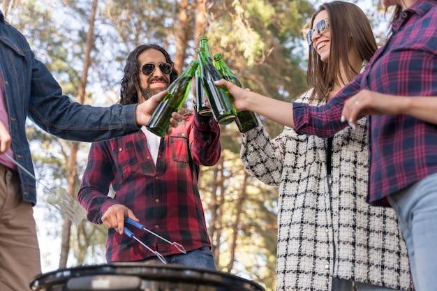 Amis, grillage avec de la bière à l'extérieur au barbecue