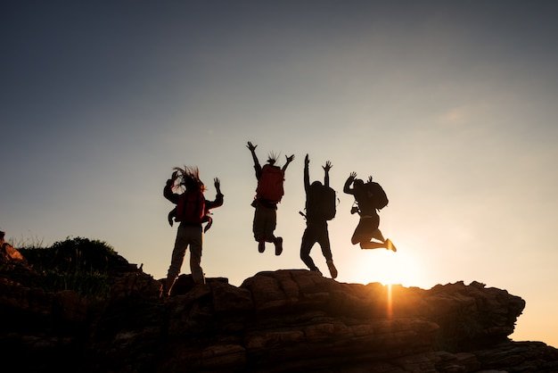 Amis de groupe d'escalade sautant sur la haute montagne et ciel coucher de soleil incroyable.
