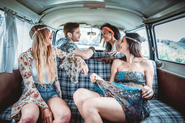 Amis heureux au volant d'une mini-fourgonnette vintage