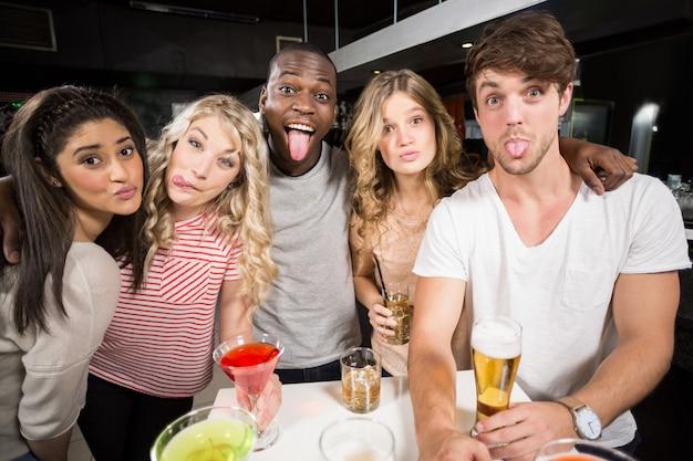 Amis heureux avec de la bière et des cocktails qui sort la langue