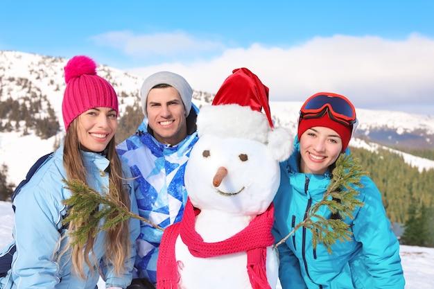 Amis heureux avec bonhomme de neige à la station de ski. vacances d'hiver