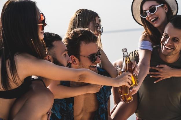 Les amis heureux avec des bouteilles profitent de l'été à la plage