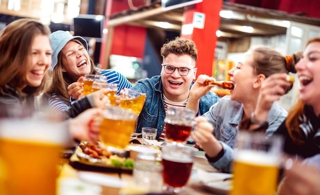 Amis heureux buvant de la bière avec de la nourriture mélangée dans un lieu intérieur