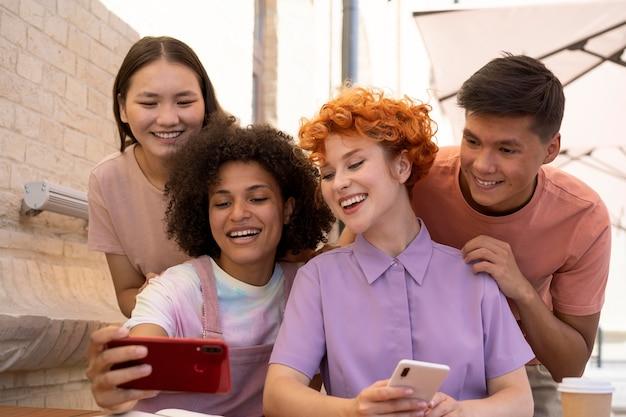 Amis heureux de coup moyen prenant le selfie