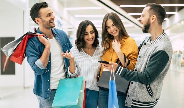 Des amis heureux et élégants avec des sacs à provisions cherchent ensemble sur le téléphone intelligent et discutent des ventes dans le centre commercial