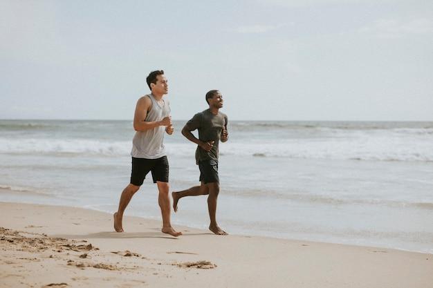 Amis heureux faisant du jogging à la plage ensemble