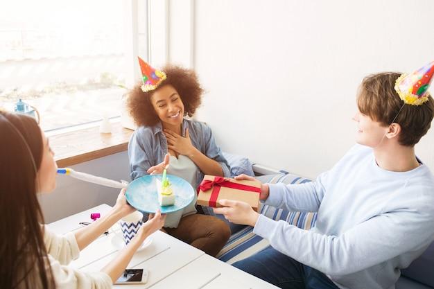 Des amis heureux fêtent leur anniversaire. ils ont des chapeaux drôles sur la tête. guy tient un cadeau tandis que la fille en pull blanc tient l'assiette avec un morceau de gâteau. afro-américaine est heureuse.