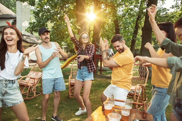 Des amis heureux ont une bière et un barbecue en journée ensoleillée