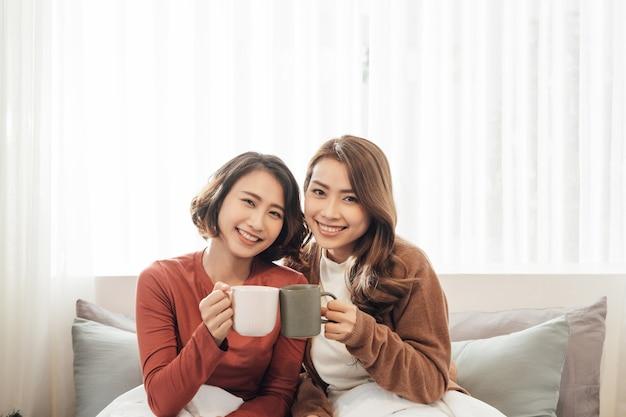 Amis heureux parlant et buvant du café et du thé assis sur un canapé à la maison