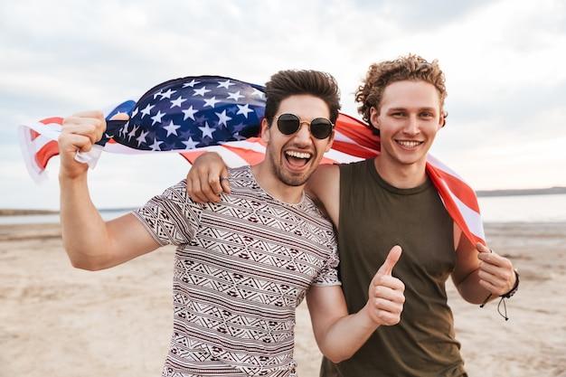 Amis heureux passant du temps à la plage, tenant le drapeau américain