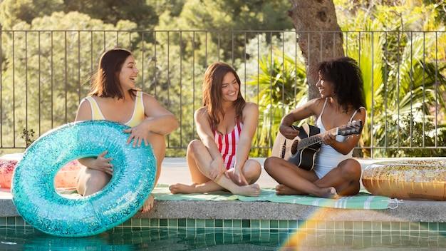 Amis heureux plein coup à la piscine avec guitare